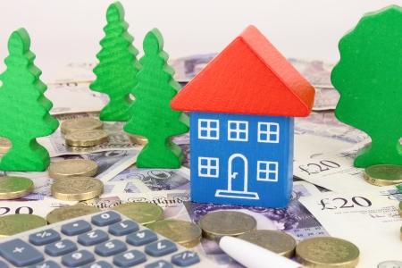 sterlina: Una casa giocattolo su soldi sterlina, con monete e una calcolatrice Archivio Fotografico