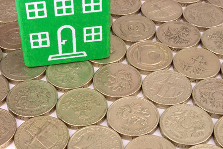 A green home on a bed of coins photo