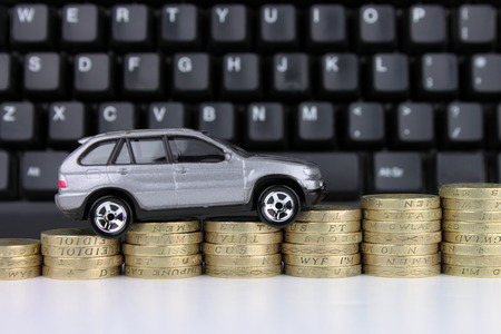 buy car: A car on a rising column of coins, with a keyboard in the background