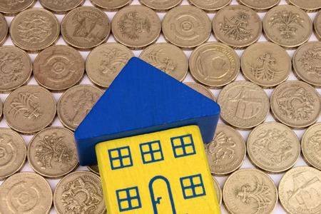 sterlina: Una casa giocattolo a forma di una freccia, su un letto di monete Archivio Fotografico