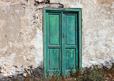 spanish house: A very old and faded, traditional green door