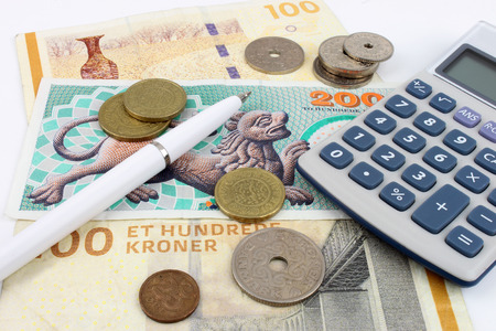 Danish Kroner notes and coins arranged with a calculator and pen