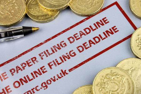 retour: UK Belastingaangifte kennisgeving met munten en een pen