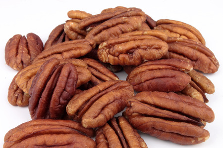 A close-up of a bunch of Pecans against a white background