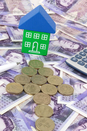 A house sitting on a pile of money, with a pen and calculator Stockfoto