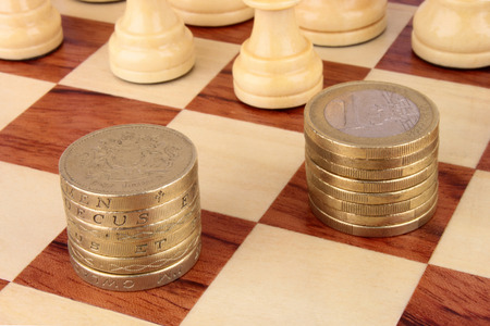 moves: A chess board with a stack of Euro and Sterling coins