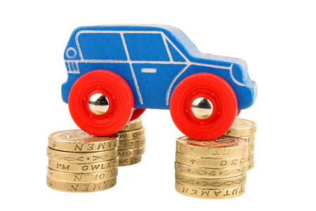 A toy car supported by coins on each wheel  Stock Photo