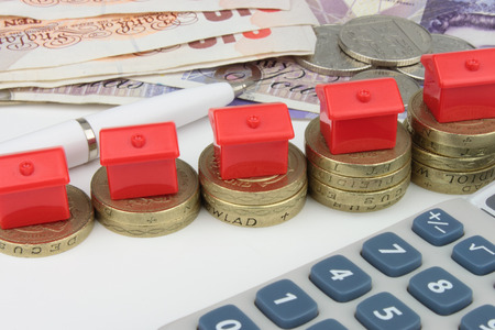 Red houses sitting on rising stacks of coins, with a pen and calculator to symbolize house finance in the U k  Stockfoto