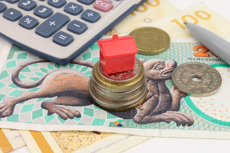 A toy house sitting on Danish Kroner notes, with coins and a calculator  A photograph illustrating Danish house costs and finance