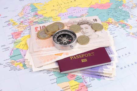 abroad: Sterling notes, coins, a compass and  a map of the world