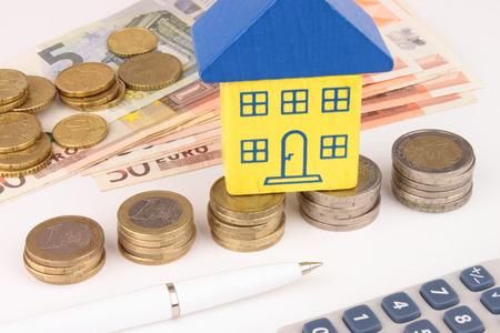 financial metaphor: Un creciente pila de monedas de euro con algunas casas en la parte superior, dinero en efectivo, la calculadora y la casa de la pluma Un Euro met�fora financiera