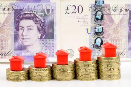 Aumento pile di monete con le case sulla parte superiore, per rappresentare un mercato immobiliare in aumento Archivio Fotografico - 30832386
