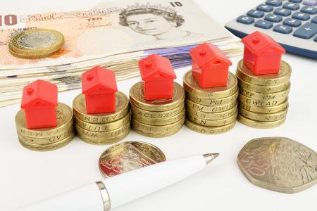 sterlina: Aumento pile di monete con case giocattolo in alto, a rappresentare finanza immobiliare Archivio Fotografico
