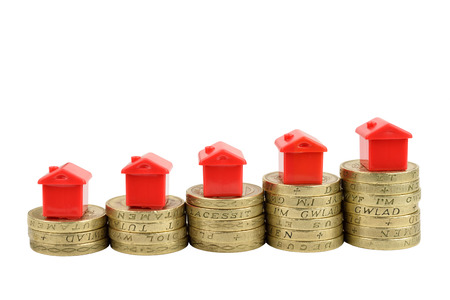 Rising stacks of coins with houses on top, to represent a rising property market