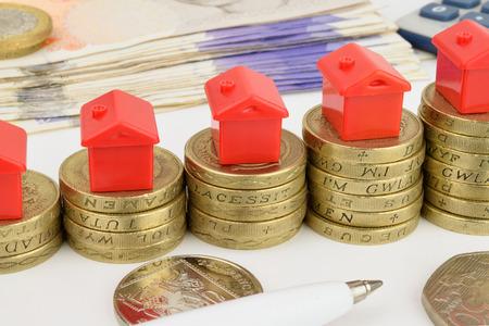 Aumento pile di monete con case giocattolo in cima, per rappresentare un mercato immobiliare in aumento Archivio Fotografico - 30832391