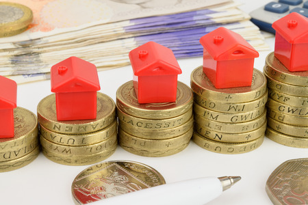 Rising stacks of coins with toy houses on top, to represent a rising property market