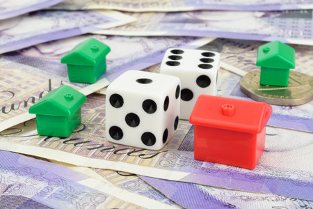 Toy houses surrounding two dice on Sterling money  A metaphor on property risk and finance  Stock Photo
