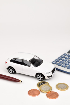 A white car on a white background with Euro coins and calculator.
