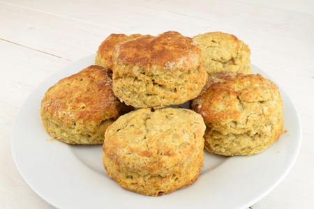 A plate of homemade apple and cinnamon scones, on a white wooden table.
