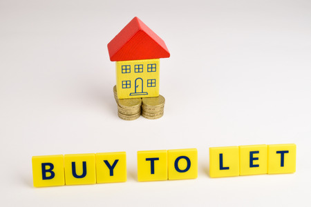 A toy house sitting on a stack of coins with the words, Stock Photo