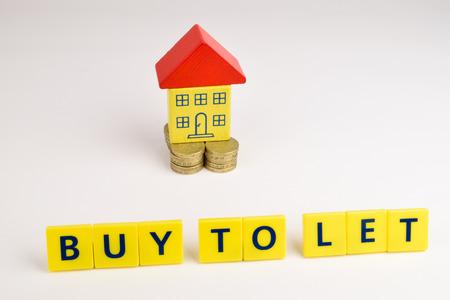 Een speelgoed huis zittend op een stapel van munten met de woorden: