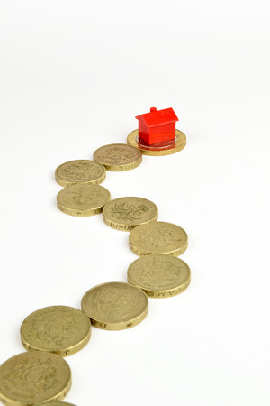 A path of coins leading to a toy red house. A metaphor on home finance. photo