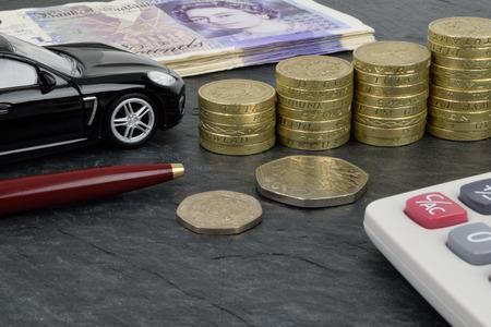 sterlina: Un finanziamento auto ancora vita su ardesia, con una macchina, monete, calcolatrice e denaro sterline.