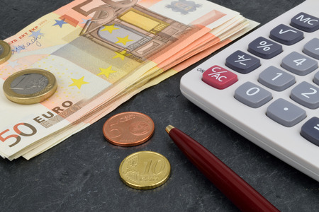 symbolize: Euro notes and coins with a calculator and pen, to symbolize European finance. Stock Photo