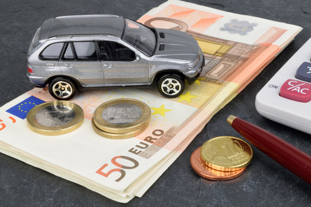 A car finance still  life with a calculator, cash and toy car on slate. Stock Photo