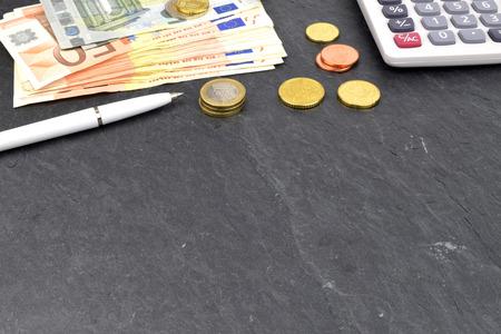 billets euros: Un agencement de pi�ces de monnaie et les billets en euros calculatrice sur ardoise. Banque d'images