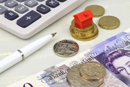 life metaphor: A still life with pound notes coins and a toy house. A metaphor on property finance.