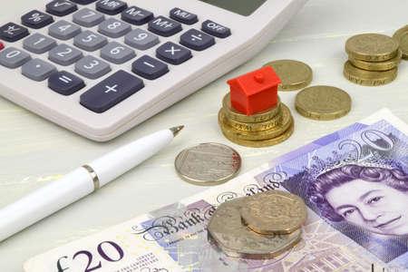 libra esterlina: Una vida inmóvil con notas de la libra monedas y una casa de juguete. Una metáfora sobre la financiación propiedad.