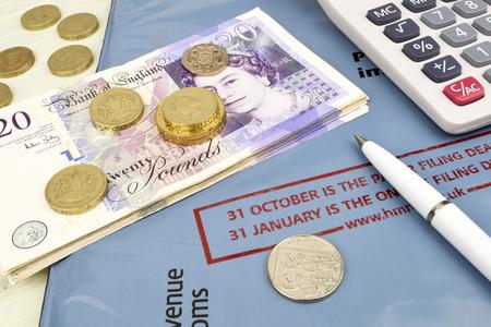 retour: Een stilleven van Uk aangifte objecten, inclusief een calculator cash en pen.