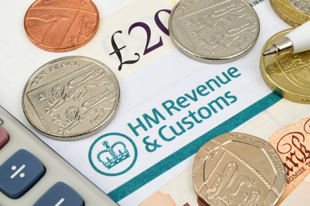 A close up of HM tax return with coins and a calculator.