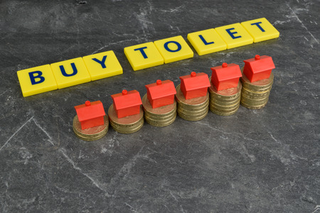 A rising stack of coins with toy houses on top and the words; Buy To Let in the background. Фото со стока
