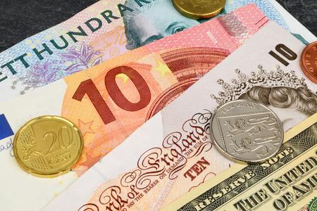 sterling: Euro, Dollaro, Sterlina Kroner e note su uno sfondo di ardesia.
