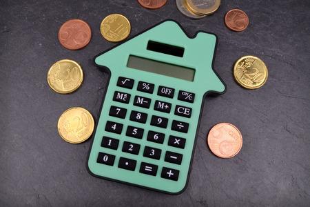 Una calcolatrice a forma di casa contro uno sfondo di ardesia, con le monete in euro intorno a esso. Archivio Fotografico - 44693373