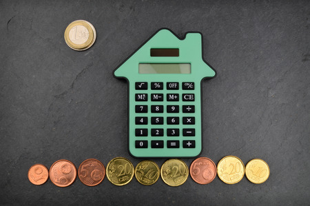 A house shaped calculator against a slate background, with Euro coins around it.