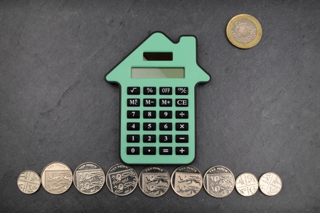 A house shaped calculator against a slate background, with Sterling coins for gound and sun. Stockfoto