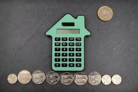 calculadora: Una casa de forma calculadora contra un fondo de pizarra, con las monedas esterlinas para gound y el sol. Foto de archivo