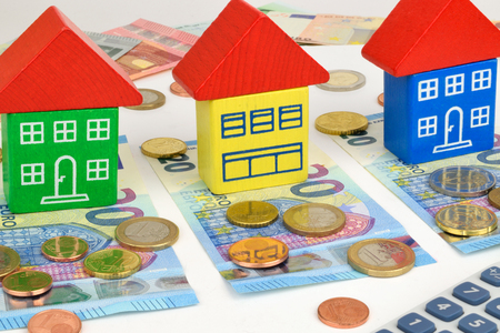 symbolize: Three toy houses sitting on Euro notes and coins, with a calculator to symbolize home finance.