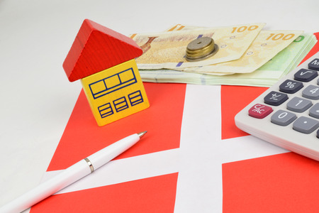Danish Kroner notes and coins, with a house, calculator to represent property finance. Stock Photo
