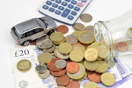 A motor finance still life with car, calculator, coins, notes and a jar.