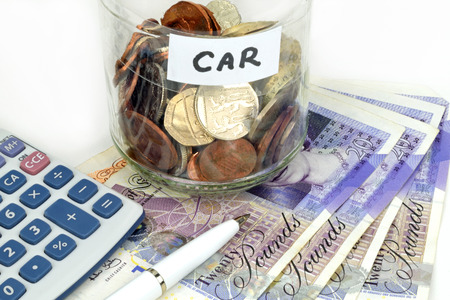 A car finance still life with jar of coins, calculator, notes and pen. Stock Photo