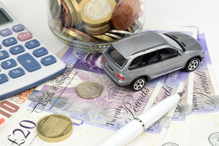 A car finance still life with jar of coins, calculator, notes, car and pen.