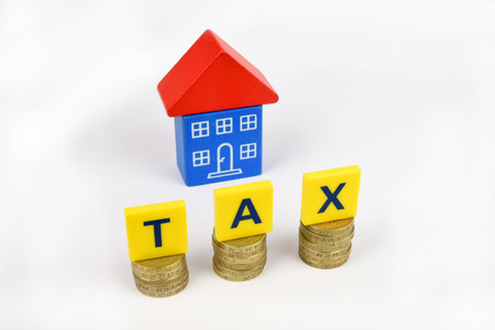 A blue and red toy house  with the letters TAX on coins in the foreground.