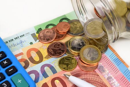 A close up financial still life of Euro banknotes, coins and a pen.