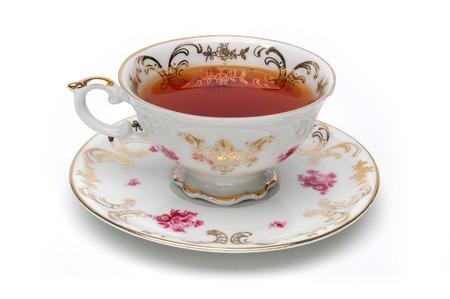 taza de te: Taza de té de antigüedades llena de té en el fondo blanco