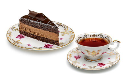 antique background: Chocolate cake and tea in antique porcelain cup on a white background