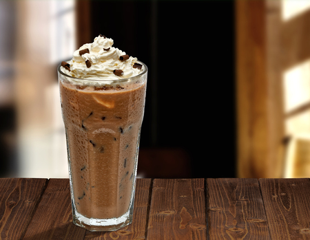 Iced coffee mocha with whipped cream on wooden table at cafe